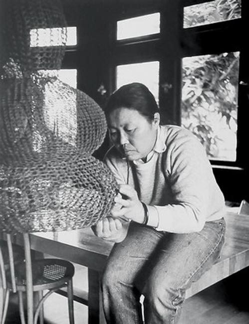 Ruth Asawa works on a crocheted-wire sculpture in her living room, ca.  1976.  Photo by Allen Nomura.