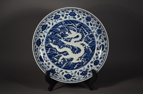 Lot 502: Important and rare, large 15th Century Chinese Ming Dynasty porcelain charger; central reverse design of writhing dragon amid crashing waves, surrounded on the cavetto with a continuous band of lotus blossoms borne on a single undulating stem with lobed leaves; the exterior with a band of five-toed dragons chasing flaming pearls; six-character Xuande Mark and of the Period; D: 49 cm, H: 9 cm (Estimate: $150,000-250,000)