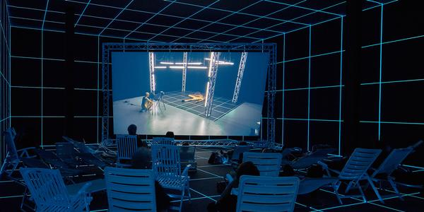 """Hito Steyerl, """"Factory of the Sun,"""" 2015.  Single channel high definition video, environment, luminescent LED grid, beach chairs, 23 minutes.  Installation view from the Venice Biennale, German Pavilion, 2015.  Image courtesy of the Artist, Andrew Kreps Gallery, New York and Esther Schipper, Berlin.  Photography by Manuel Reinartz."""