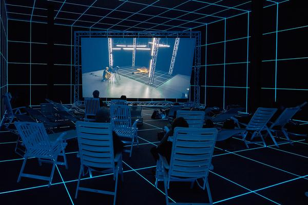 "Hito Steyerl, ""Factory of the Sun,"" 2015.  Single channel high definition video, environment, luminescent LED grid, beach chairs, 23 minutes.  Installation view from the Venice Biennale, German Pavilion, 2015.  Image courtesy of the Artist, Andrew Kreps Gallery, New York and Esther Schipper, Berlin.  Photography by Manuel Reinartz."
