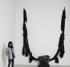 "Barbara Chase-Riboud with ""The Albino"" (aka ""All That Rises Must Converge/Black""), 1972, bronze with black patina, silk, wool, linen, and synthetic fibers, 138"" x 137"" x 30"" / 350.5 x 348.0 x 76.2 cm"