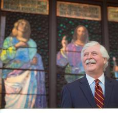 William Vareika in front of John La Farge stained glass windows he and his wife Alison donated to the McMullen Museum, Boston College.