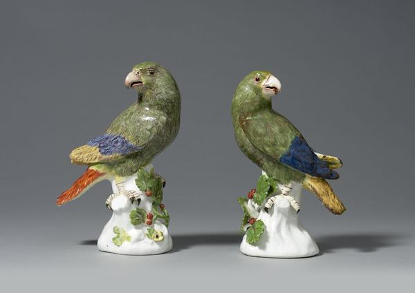 An Important Pair of Early Meissen models of South American Parrots, modelled by Johann Joachim Käendler each perched upon a white tree stump and looking to one side, beautifully naturalistically coloured, each representing a Green Amazon Parrot painted in green with puce detailing to its plumage, and with red, blue and yellow wing tips and tail, the tree stumps issuing leafy berried branches.  Circa 1738-42 1st height: 7 ¾ in (19 ½ cms)2nd height: 7 ½ ins (19 cms)