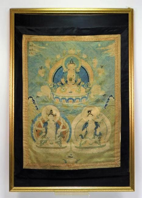 Chinese Qing Dynasty (1644-1912) or earlier embroidered tapestry depicting three Buddha figures seated on lotus thrones, nicely housed in a 37 ¾ inch by 25 ½ inch frame ($12,500).