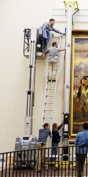 A copy of French artist Louis Charles-Auguste Couder's Siege of Yorktown (1781) being installed at the Museum of the American Revolution.