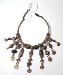 Decorative antique necklace comprised of Islamic glass beads, mostly circa 8th-12th century AD, with the beads strung together with plated coin replicas, brass breads and wire (est.  700-$1,000).