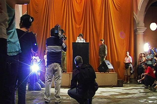 Tatlin's Whisper, #6 (Havana Version), 2009 Stage, podium, microphone, loudspeakers, curtain, two people dressed in military fatigues, dove, audience, and 200 disposable cameras Wifredo Lam Center, Havana