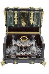 19th century French Napoleon III tantalus or cave a liqueur (either way, a decanter set), in an ebonized wood oxbow cabinet having four decanters and sixteen glasses (est.  $1,000-$2,000).