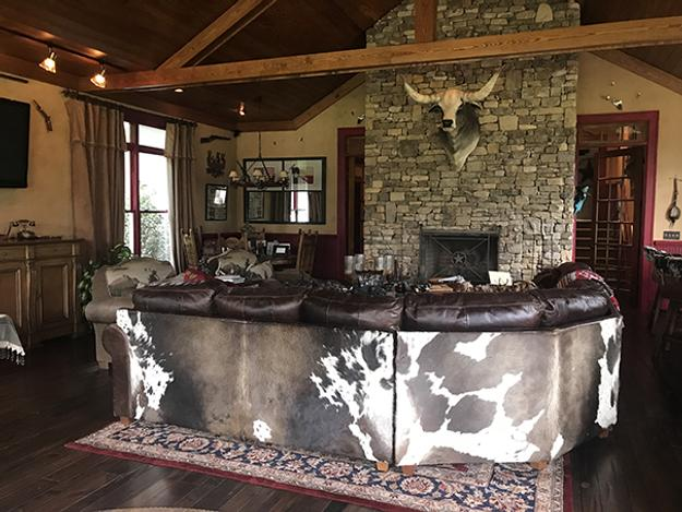The sprawling, western-themed ranch property includes a home, a separate 'saloon' entertaining area guest house (interior shown), a wine cellar, horse stables, stocked ponds and outbuildings.