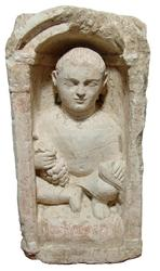 Large Coptic limestone funerary stela, 4th or 5th Century, depicting a youth kneeling upon a soft chair or pillow within a domed niche supported by Corinthian columns (est.  $6,500-$9,000).