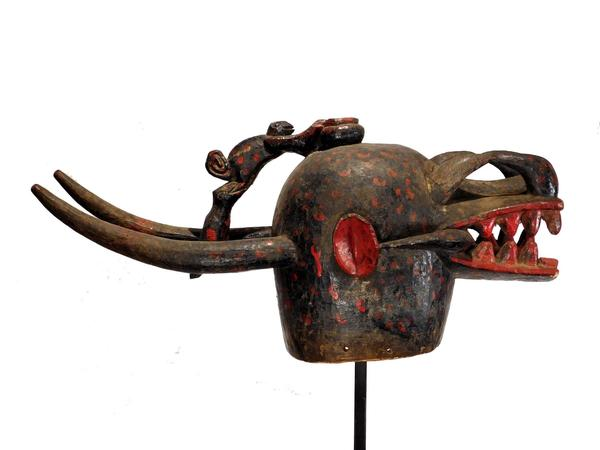 Senufo Kulonugo fire spitter, a massive wood carving covered with black paint and adorned by additions of red paint.  Atop the head is a carved offering bowl (est.  $2,500-$5,000).