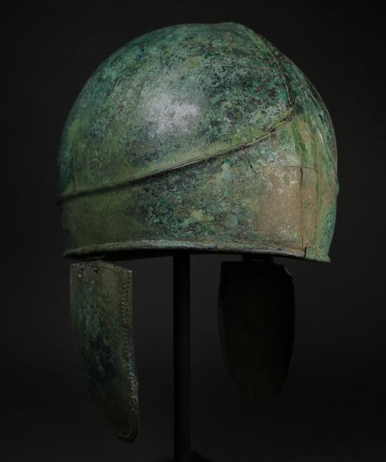 Rare two-part Greek bronze Chalcidian helmet, circa 500-300 BC, Classical to Alexander the Great period.  High-crested crown and hinged cheek pieces.  Perfect condition with beautiful patina.  Estimate £15,000-£30,000