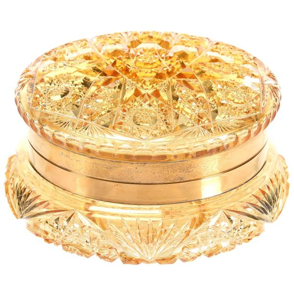 ABCG round dresser box in a solid gold color with gilt metal fittings, attributed to Union Cut Glass and purchased from the Julian De Cordova Museum in Lincoln, Mass, 3 ½ inches by 6 ¼ inches.