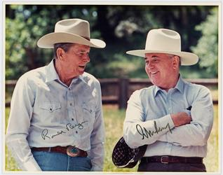 Original color photograph of Ronald Reagan and Russian leader Mikhail Gorbachev, showing the two men wearing Western hats in an outdoor setting, signed by both (est.  $3,500-$4,000).