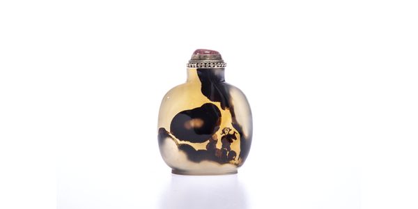 From SUSAN PAGE.  Agate, honey colour with natural darker inclusions minimally carved to reveal the silhouette of a scholar inscribing into rockwork, with a tree to one side.  1780-1850.