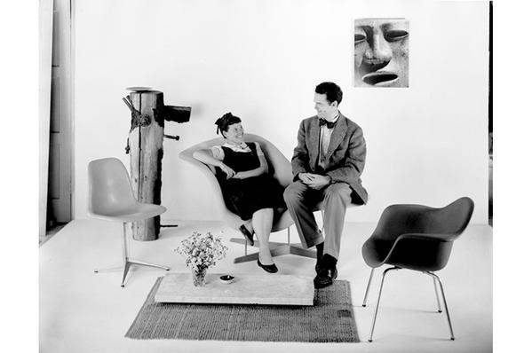 Charles and Ray Eames sitting on the La Chaise prototype, 1948.  © Eames Office LLC
