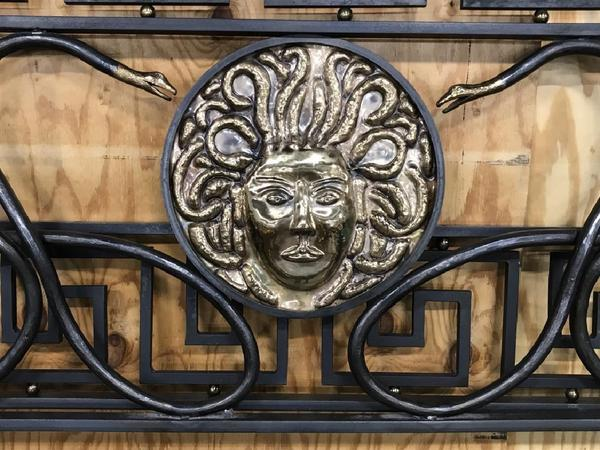 A custom made Versace bed frame replica ($5/10,000) made by an artisan metalworker in Maine is crafted from iron, bronze and brass.  It features an exact detailing of a Medusa head, framing snakes, Greek key design and originally cost $40,000; 70 by 82 inches.