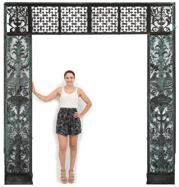 This unique pierced decorated bronze entryway, weighing several hundred pounds ($20/30,000) features a transom with geometric quatrefoil decorated panels and filigree decoration, 125 ½ by 111 1/2 inches.
