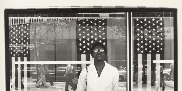Ming Smith, America seen through Stars and Stripes, New York City, New York, printed ca.  1976.  Gelatin silver print, sheet: 15 3/4 × 20 in.  (40.01 × 50.8 cm), image: 12 1/2 × 18 1/2 in.  (31.75 × 46.99 cm).  Virginia Museum of Fine Arts, Adolph D.  and Wilkins C.  Williams Fund, 2016.241.  © Ming Smith