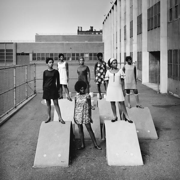 "Photo shoot at a public school for one of the AJASS-associated modeling groups that emulated the Grandassa Models and began to embrace natural hairstyles, by Kwame Brathwaite, in ""Black is Beautiful: The Photography of Kwame Brathwaite,"" at MoAD."