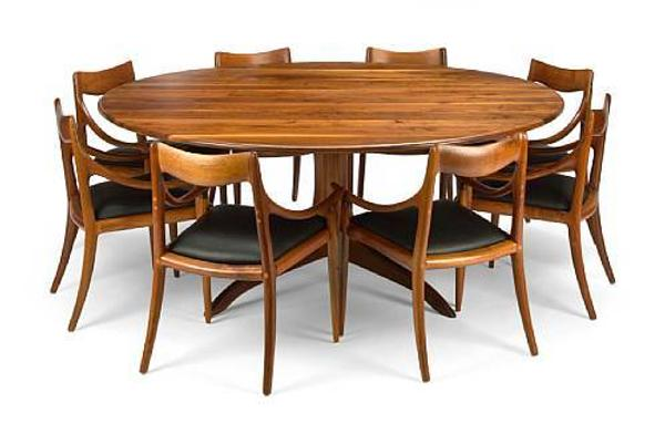 Sam Maloof (American, 1916-2009), 1970-71, circular dining table and eight chairs in walnut, sold for $39,650 inclusive of Buyer's Premium.