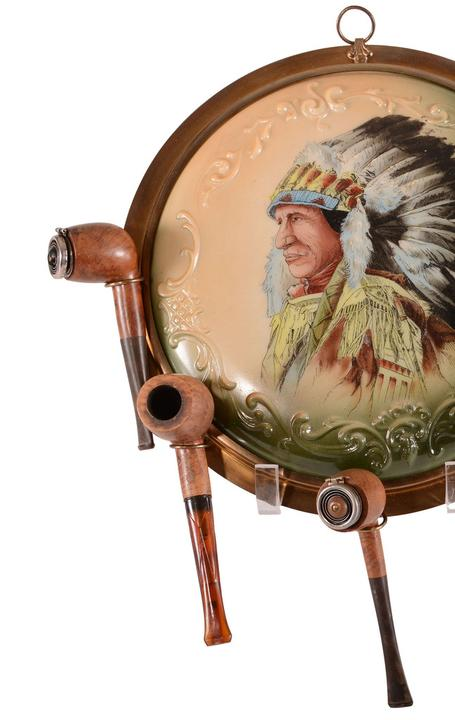 Unmarked Wave Crest pipe holder plaque in green and cream tones with a portrait of an Indian in full headdress, set in a brass frame holding five Wooden English pipes included in the lot ($13,000).
