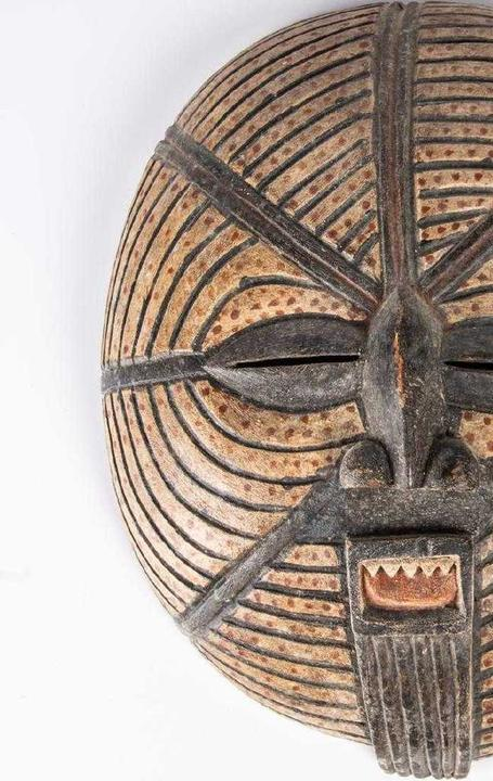 Luba tribe (Democratic Republic of Congo) carved and painted wood moon mask, 20th century, with almond shaped eyes, a small nose and prominent mouth, 17 ½ inches tall (est.  $80-$120).