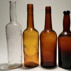 Set of four 1800s bourbon and whiskey bottles, including a rare J.  Moore Brown Old Bourbon, a Roanoke Rye brown, a blob top brown and a clear Old Quaker Club Whiskey (est.  $350-$1,000).