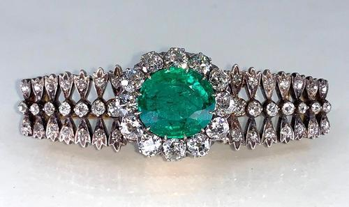 Antique Colombian emerald, gold, diamond and platinum brooch with a bracelet top and a center oval-cut emerald, surrounded by twelve old European cut diamonds (est.  $5,000-$7,000).