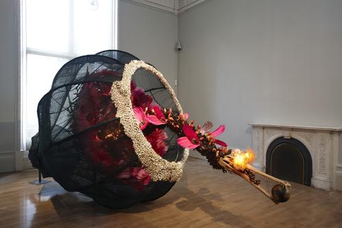 Rina Banerjee, The world as burnt fruit—When empires feuded for populations and plantations, buried in colonial and ancient currency a Gharial appeared from an inky melon—hot with blossom sprang forth to swallow the world not yet whole as burnt fruit, 2009.  Fans, feather, cowrie shells, resin alligator, skull, globe, glass vials, light bulbs, gourds, steel wire and Japanese mosquito nets, 90 × 253 × 90 inches.  Kiran Nadar Museum of Art, New Delhi, India.