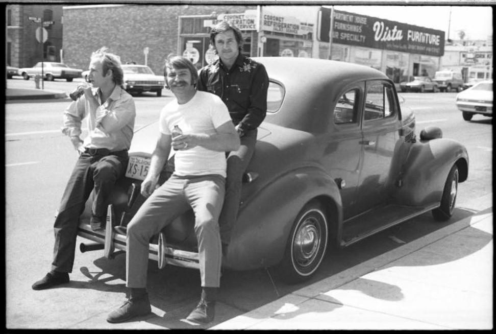 Joe Goode, Jerry McMillan (self-portrait), and Ed Ruscha with Ed's 39 Chevy, 1970.  Courtesy the artist and Craig Krull Gallery.