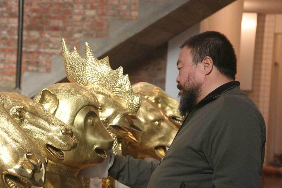 Ai Weiwei in his Beijing studio examining early versions of heads from Circle of Animals/Zodiac Heads: Gold, 2010